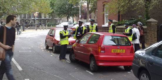 An image of five traffic wardens trying to give a ticket to one red car.