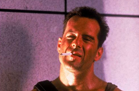 An image of Bruce Willis in the original Die Hard with a cigarette in his mouth