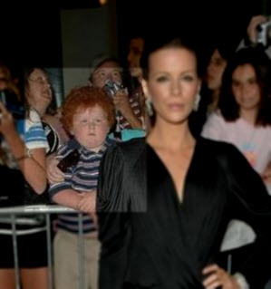An image of a ginger kid in the background shot of the beautiful actress Kate Beckinsale on the red carpet