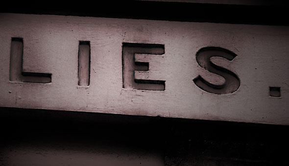 An image of the word Lies carved into masonary on the side of a building