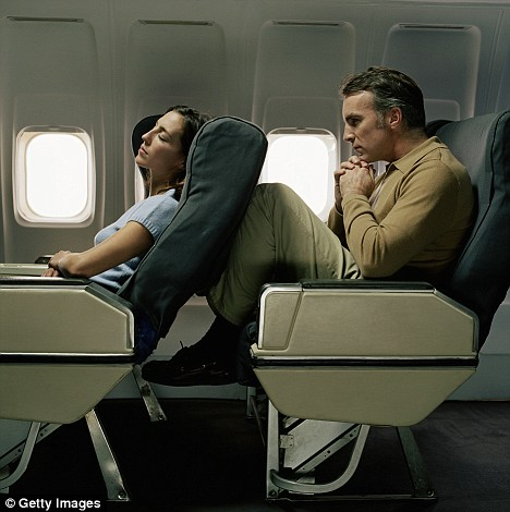 An image of a lady in a airplane seat who has fully reclined onto the other male passenger behind her.