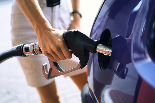An image of a lady filling up a car