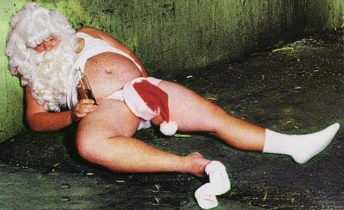 An image of a drunk, semi-naked Santa slumped holding a beer