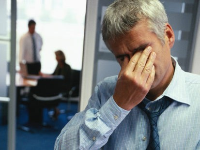 An image of a man rubbing his eyes, stressed at work.