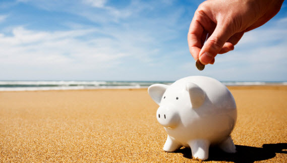 An image of a Piggy Bank on a beach which represents budget travelers