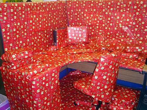 An Image of an office space completely wrapped up in christmas wrapping paper.