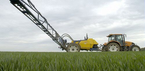 An image of a tractor spraying pesticides on a crop