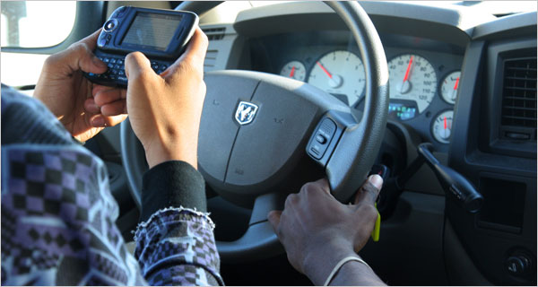 An image of a driver texting whilst someone else holds the wheel.