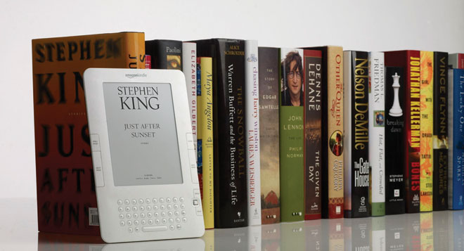 An image of a Kindle leaning against a row of books that can be downloaded on the Kindle Device