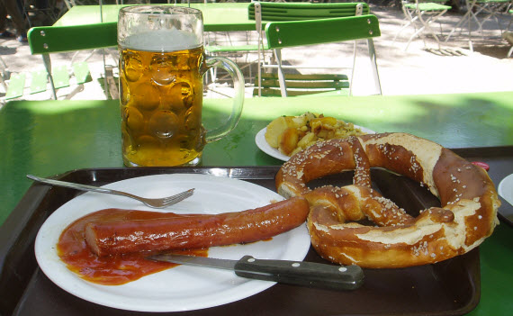 An image of a half litre beer with a pretzel in Munich