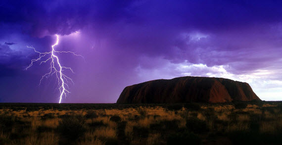 An image of the iconic Australian natural wonder that is Ayers Rock with lightning next to it